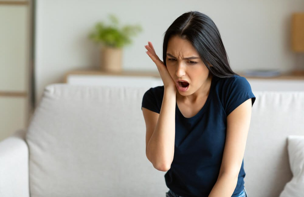 Toothache: A woman suffering from severe tooth pain   Emergency Dentist in Croydon