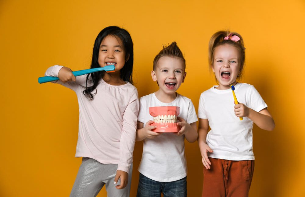 Three children with toothbrushes and a Dental implant model   Pediatric dentist near you